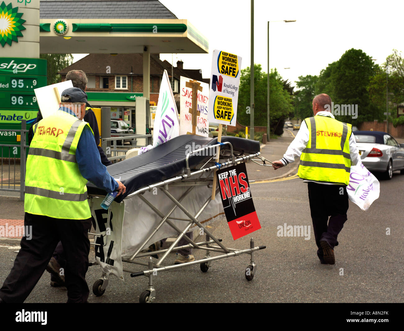 NHS Protest Against Hospital Closure Srewards Pushing NHS Trolley in the Street to Epsom General Hospital  Surrey - Stock Image