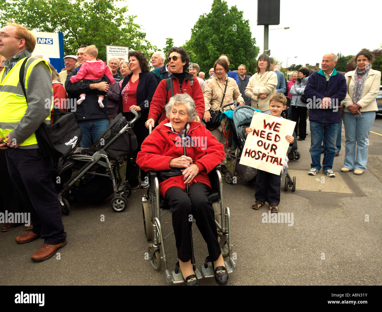 NHS Protest Against Hospital Closure Srewards Outside Epsom General Hospital Protester in Wheelchair NHS Trolley - Stock Image