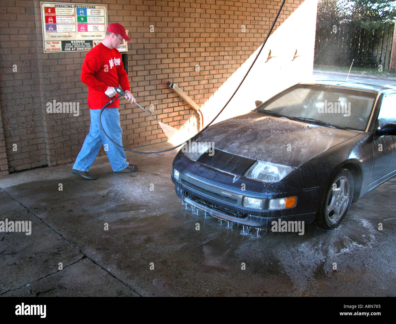 Man in self serve car wash cleaning his SUV Stock Photo
