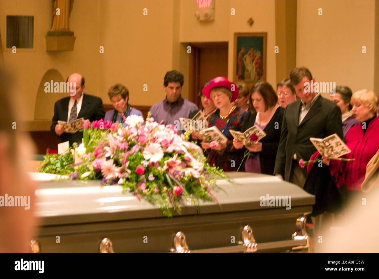 Catholic funeral stock photos catholic funeral stock images alamy casket with flowers and funeral friends singing a hymn st joan of arc catholic church izmirmasajfo