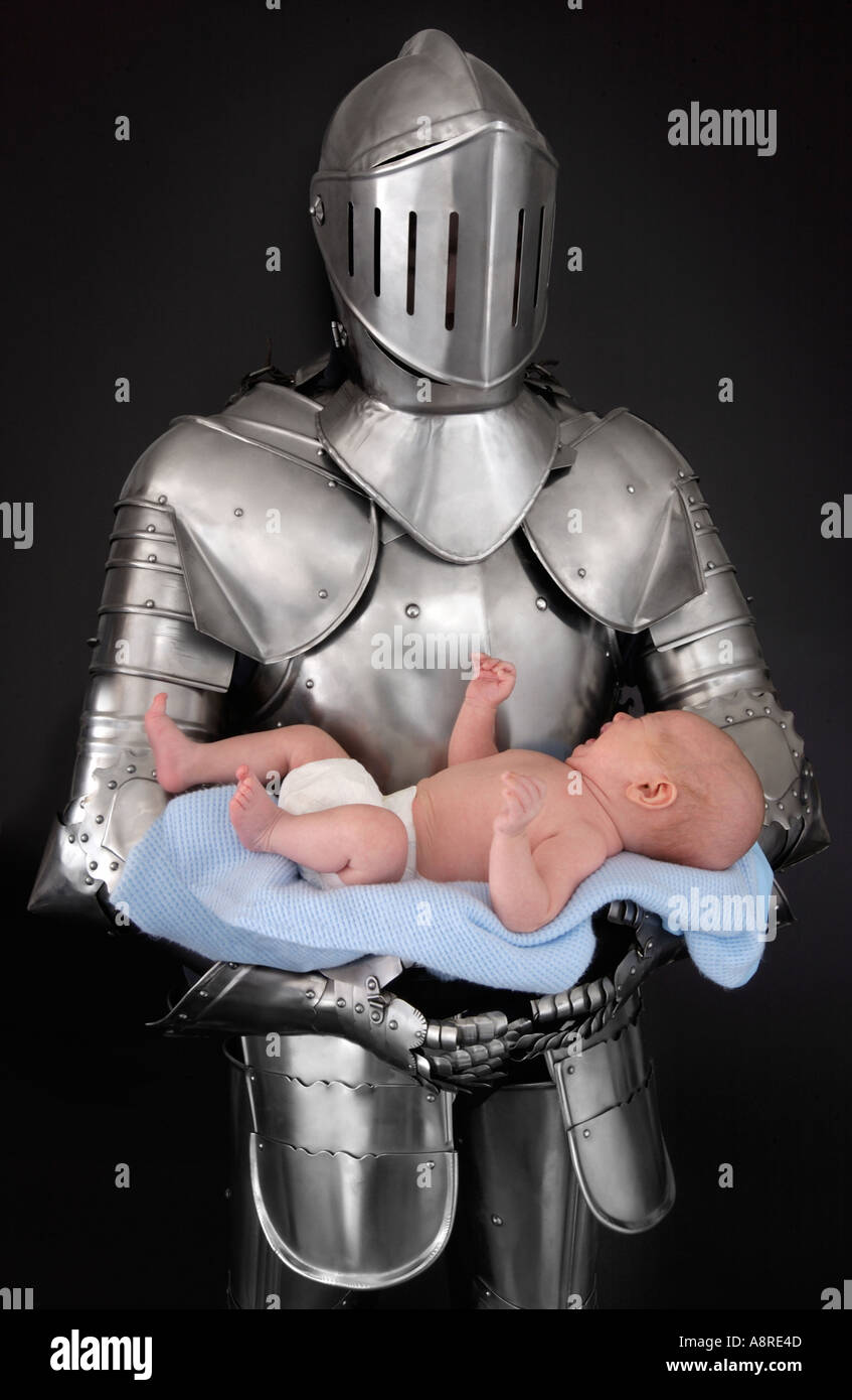 Knight in armor suit holding baby - Stock Image