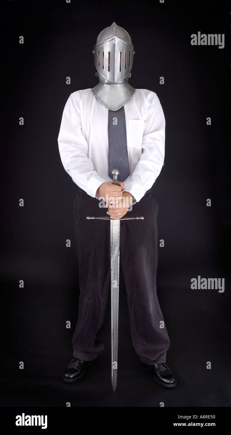 Business man wearing knight helmet and sword - Stock Image
