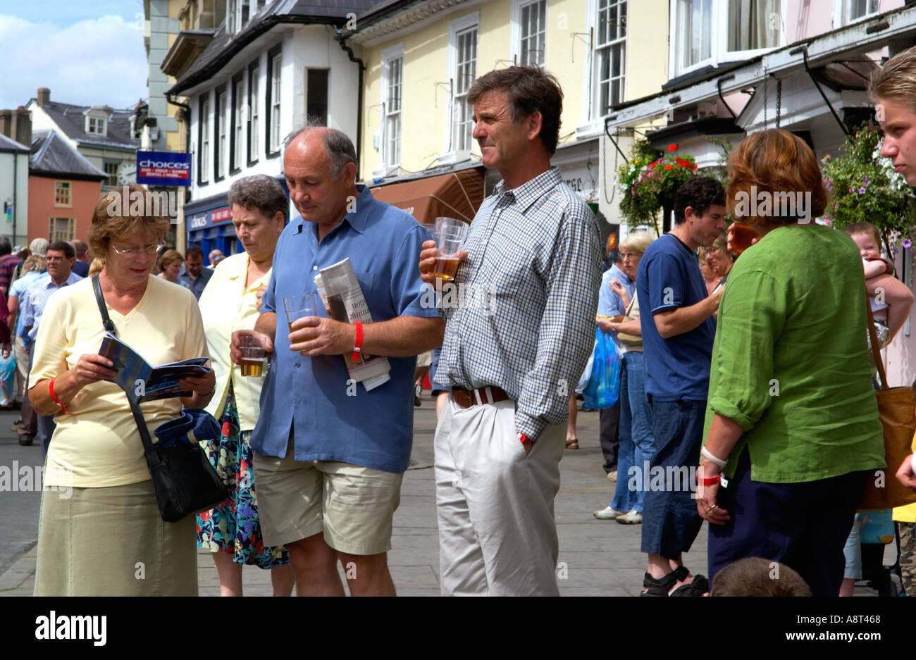 Fans standing on the street in sunshine drinking beer and reading programme during the jazz festival in Brecon Powys Wales UK - Stock Image