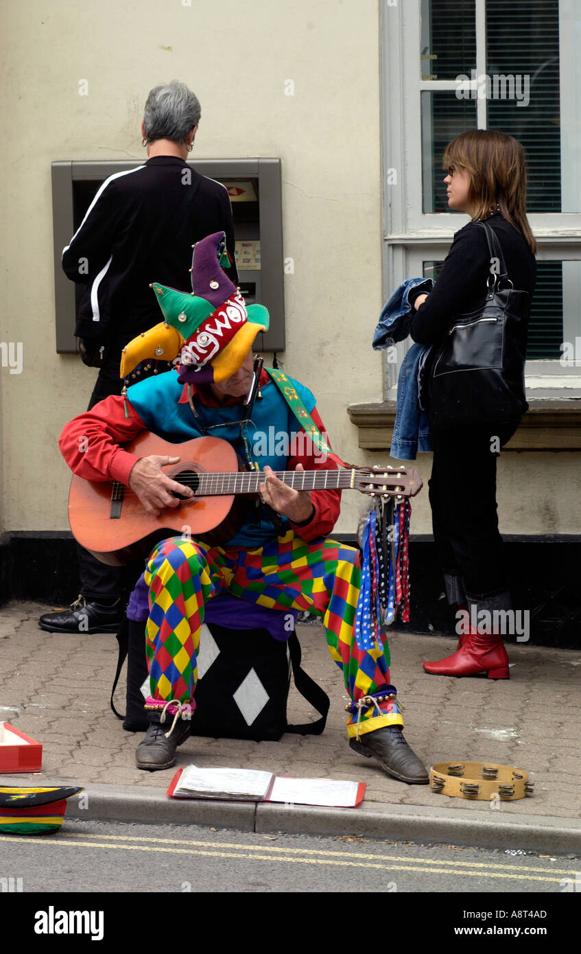 Busker on pavement outside the HSBC Bank ATM cash machine on high street in Hay on Wye Powys Wales UK Stock Photo
