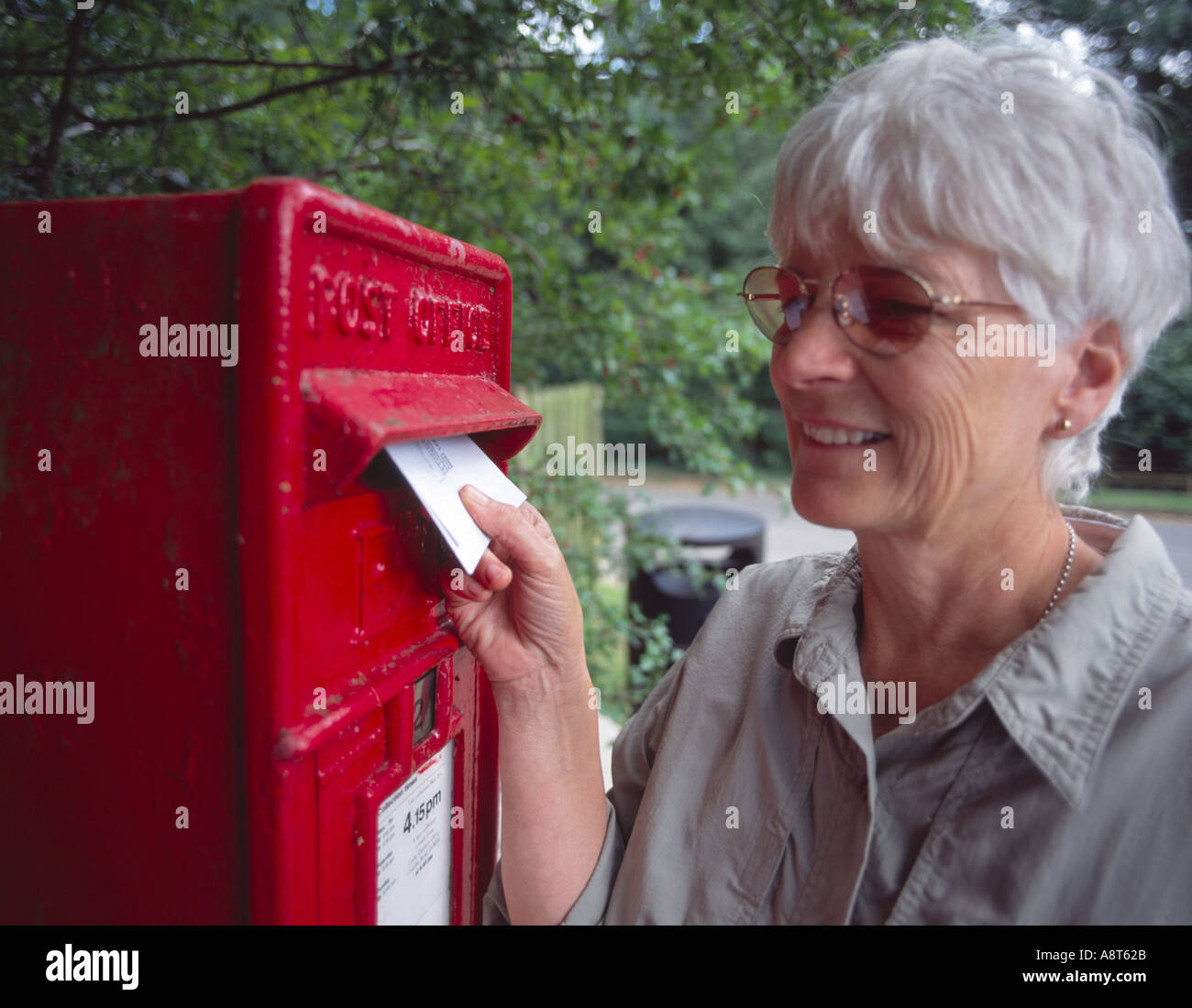 elderly woman posting a letter in traditional red British letter box in the country Stock Photo