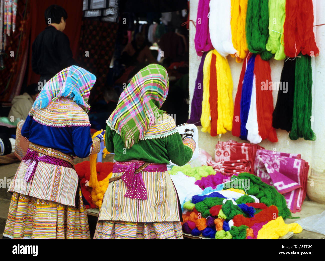 Two Flower Hmong women looking at brightly coloured wools at the Sunday market, Bac Ha, NW Viet Nam Stock Photo