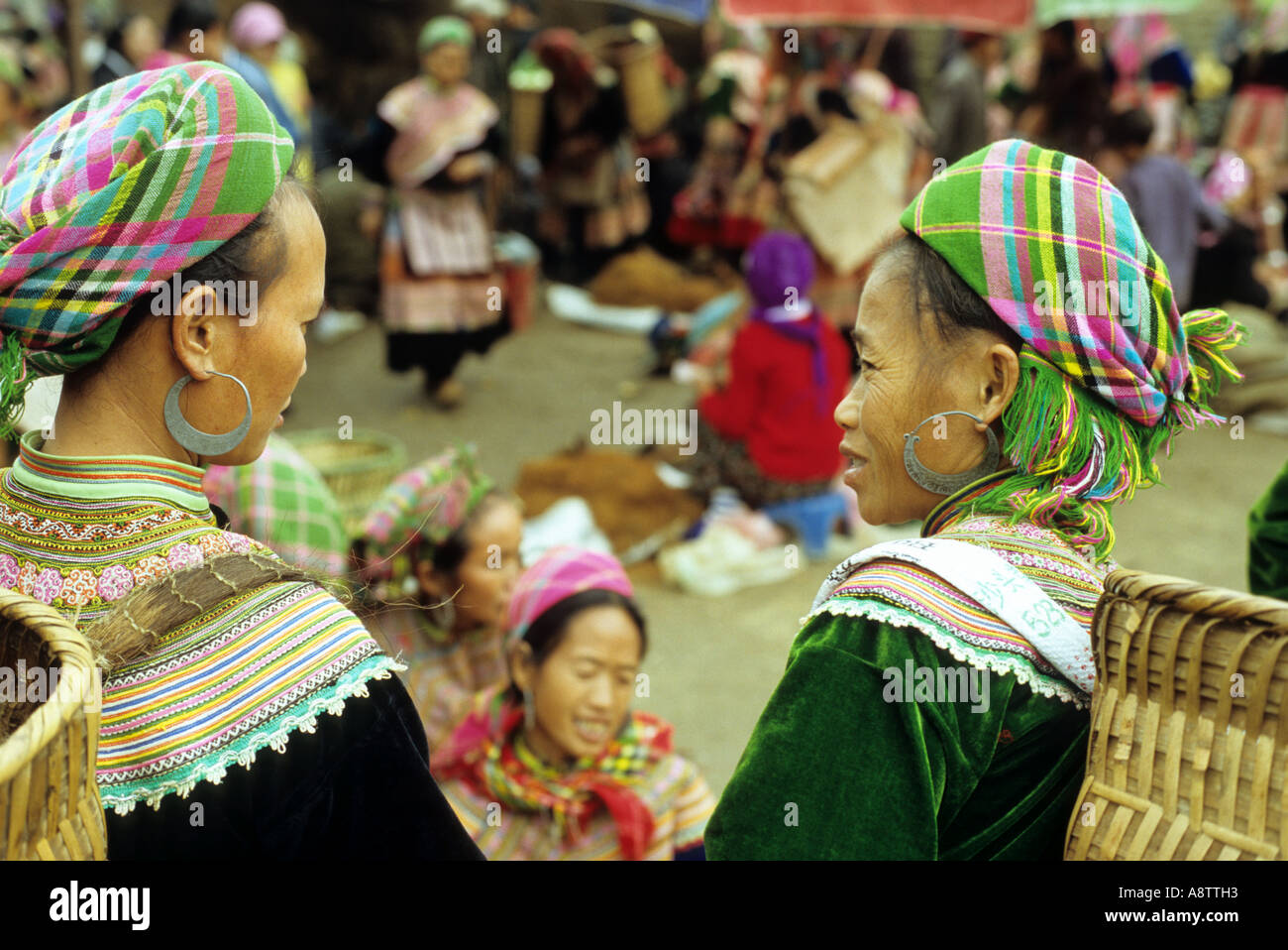 Two Flower Hmong women in colourful traditional clothing talking at the Sunday market, Bac Ha, NW Viet Nam Stock Photo