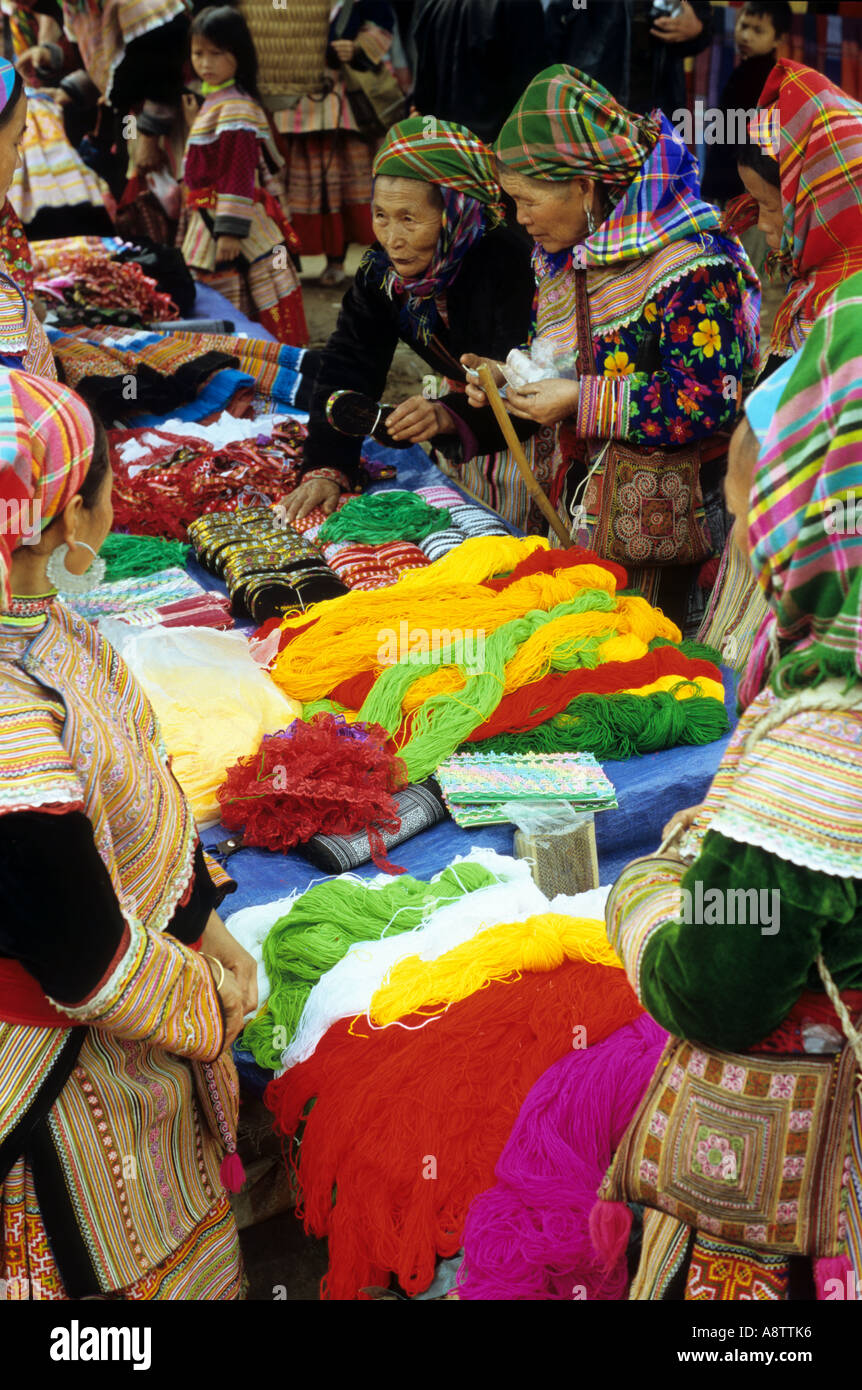 Traditionally dressed Flower Hmong women at a wool stall at the Sunday market, Bac Ha, NW Viet Nam Stock Photo