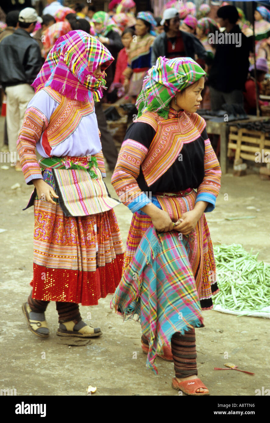 Two young traditionally dressed Flower Hmong women walking through the Sunday market, Bac Ha, NW Viet Nam Stock Photo