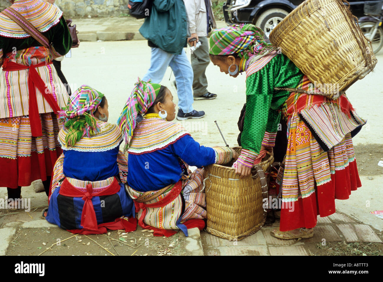 Four traditionally dressed Flower Hmong women at the roadside, Sunday market, Bac Ha, NW Viet Nam Stock Photo