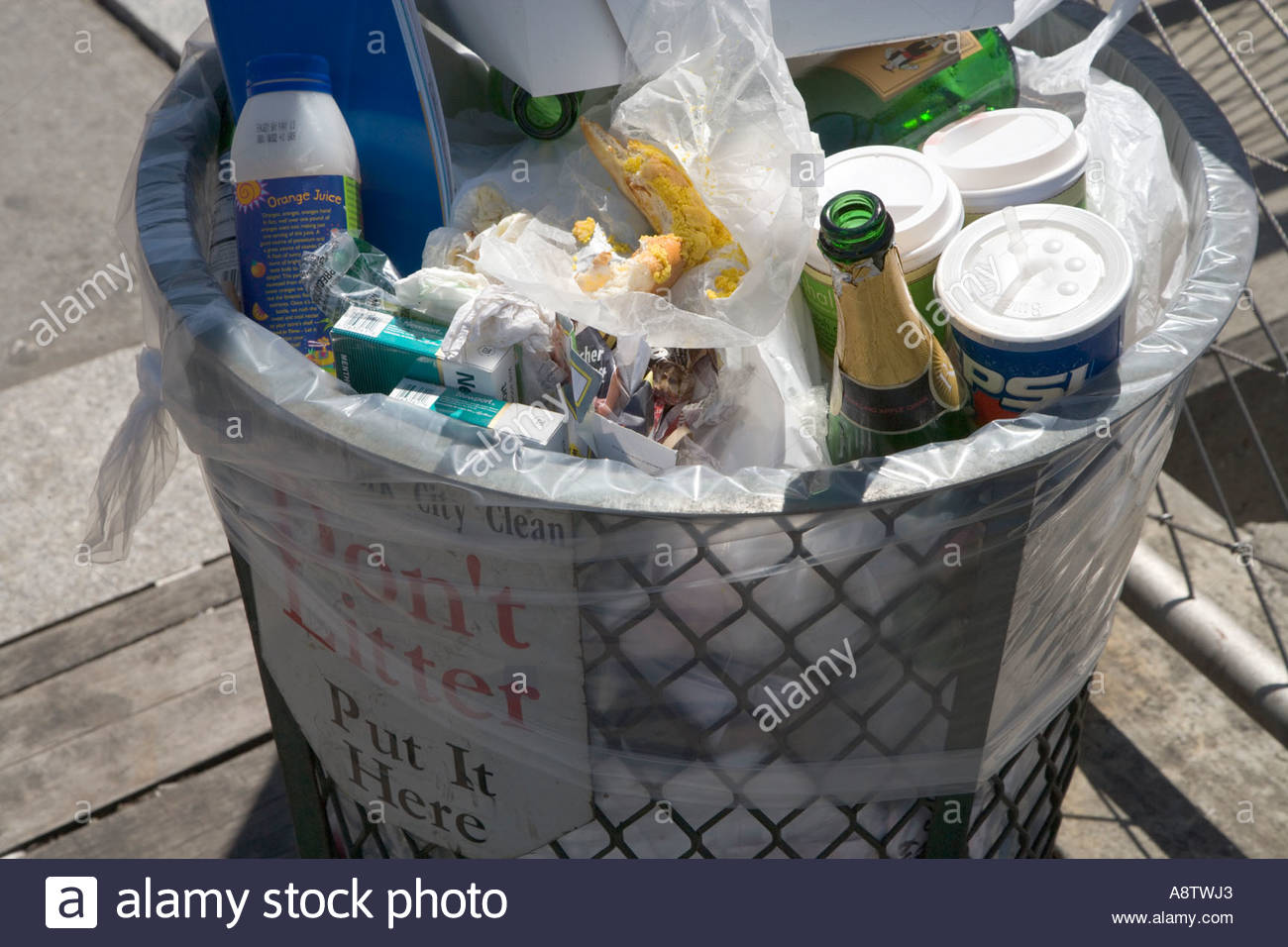 A Overflowing Trash Can Will With All Sorts Of Rubbish Including Beer Bottles