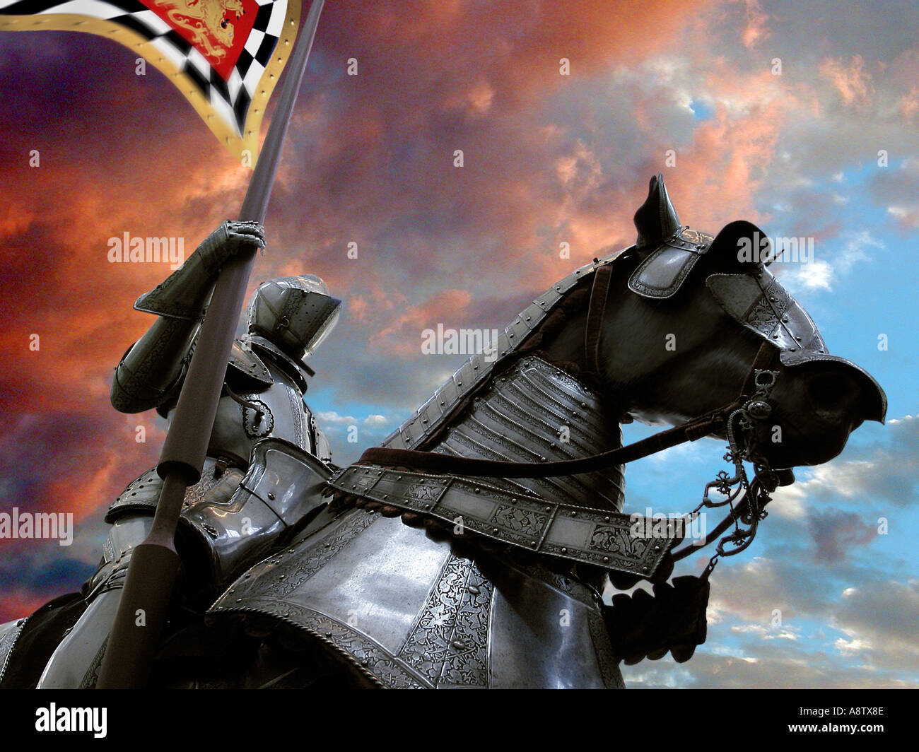 A knight in shining armor on his black armored horse holding a flag possibly preparing to joust - Stock Image