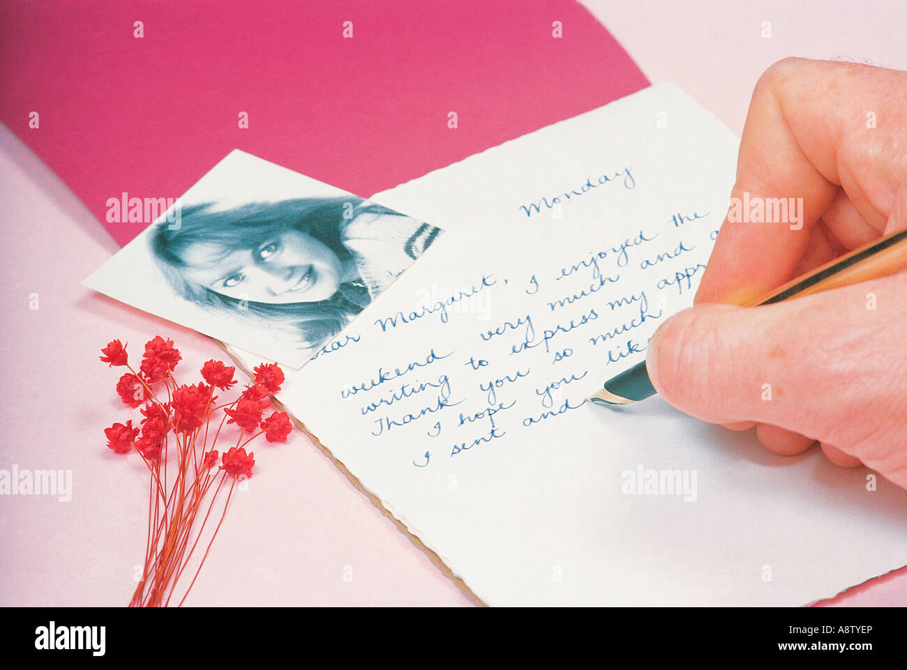 Close-up of man's hand writing a love letter. - Stock Image