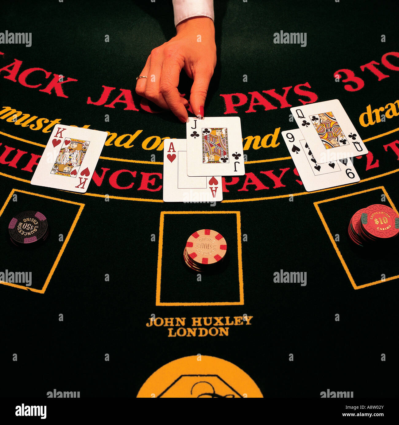 Close-up of female dealer's hand dealing cards on Blackjack table. - Stock Image