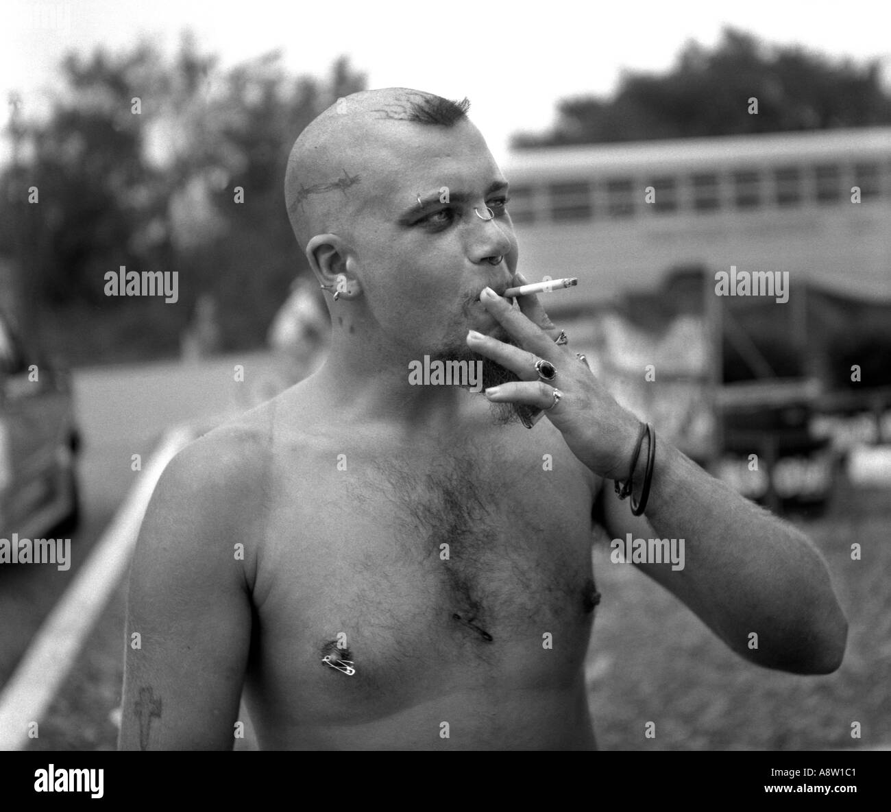 Man with body piercings smoking cigarette generation X at Woodstock 1994 music festival - Stock Image