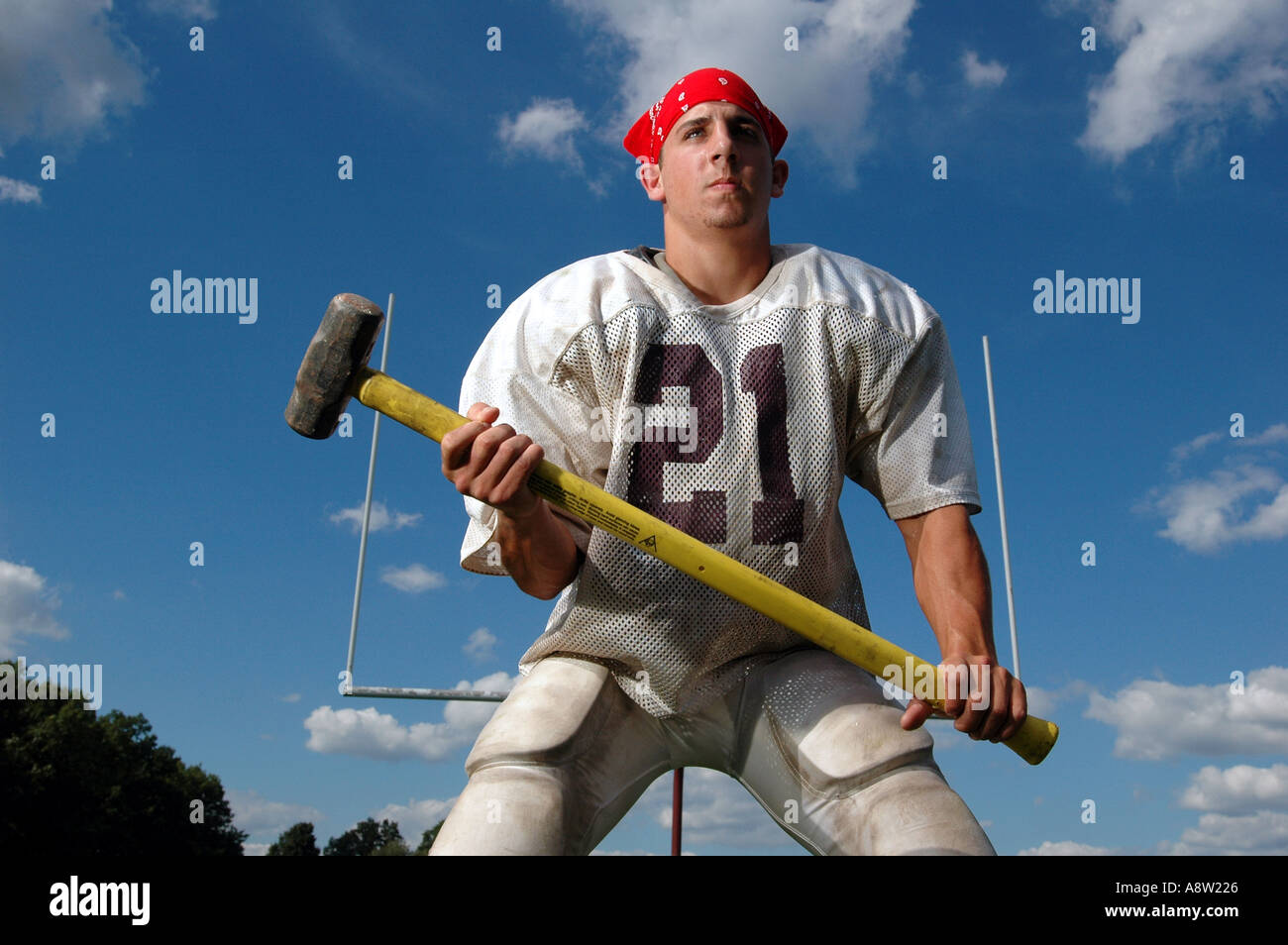 A tough football player holding a sledge hammer - Stock Image