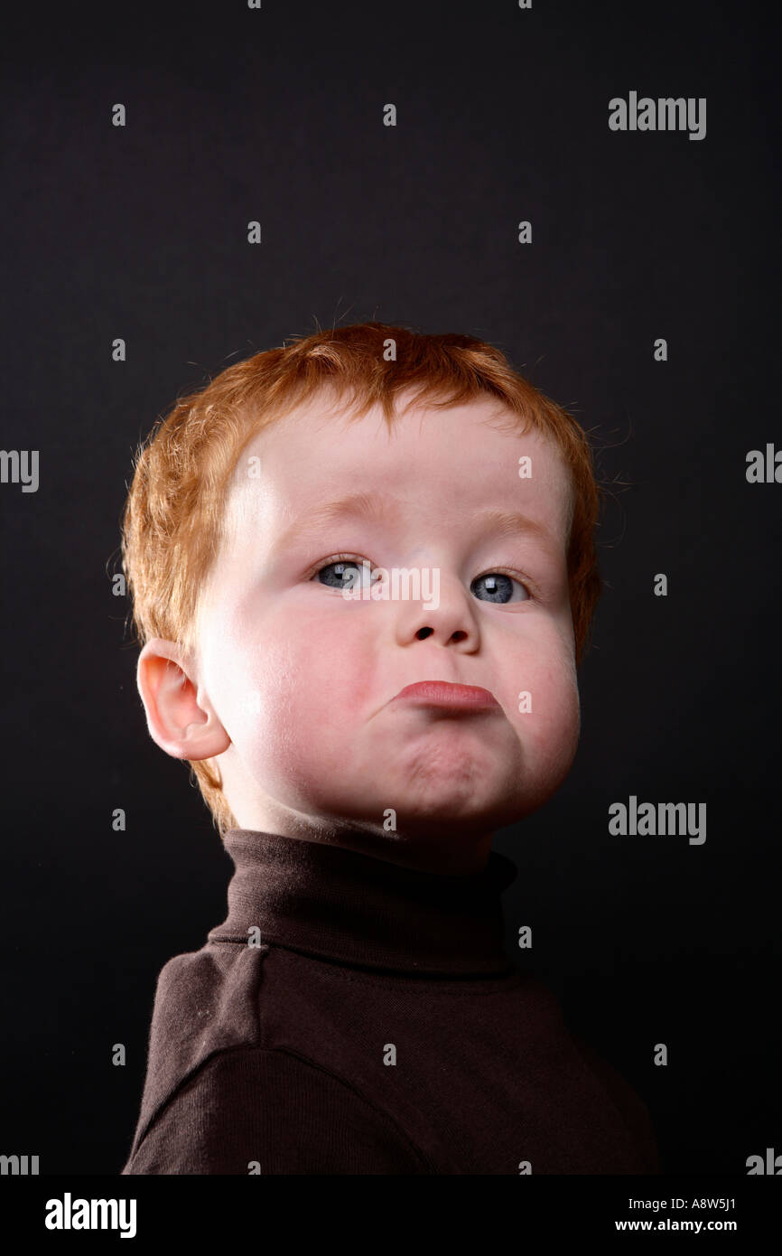 The face of a toddler with red hair Looking miserable - Stock Image
