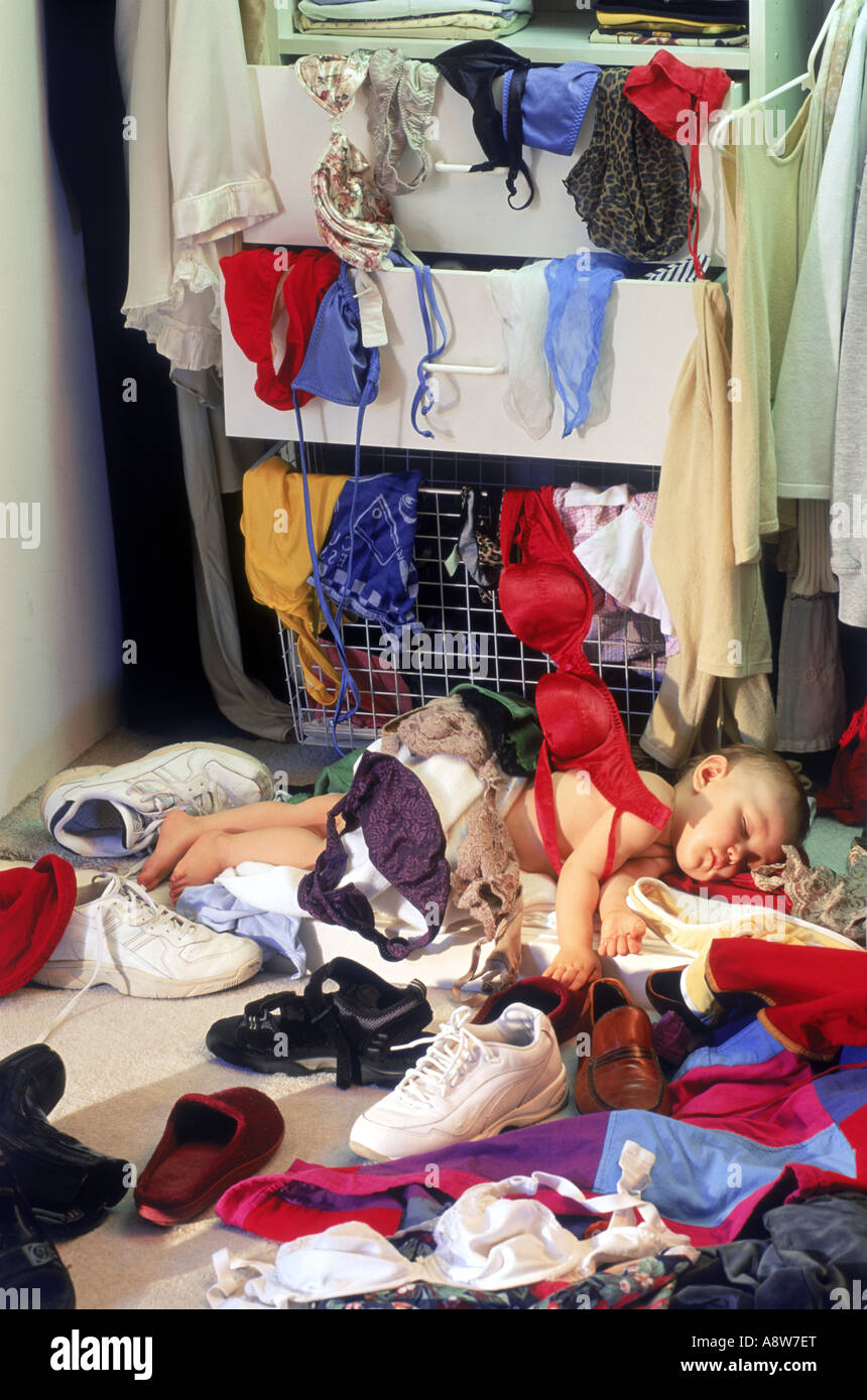 Child in parent's bedroom closet resting after making a huge mess of shoes and clothing - Stock Image