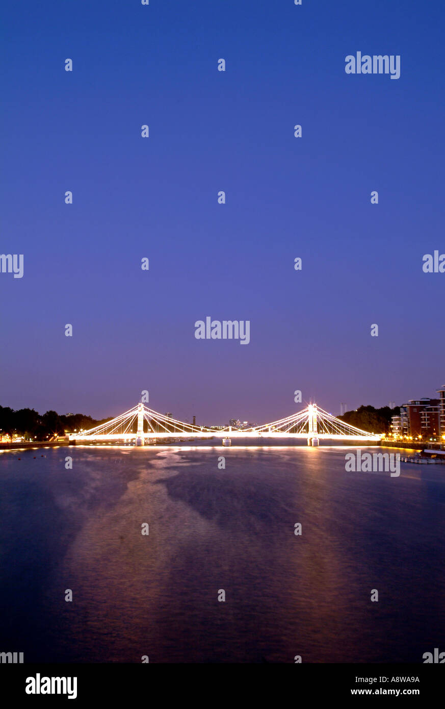 The Albert Bridge over the Thames River in London at dusk. - Stock Image