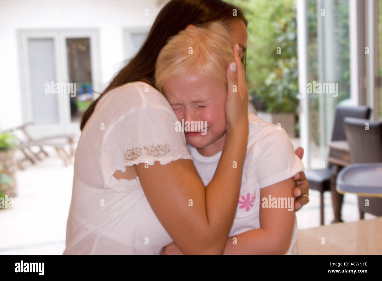 mother comforting crying child - Stock Image