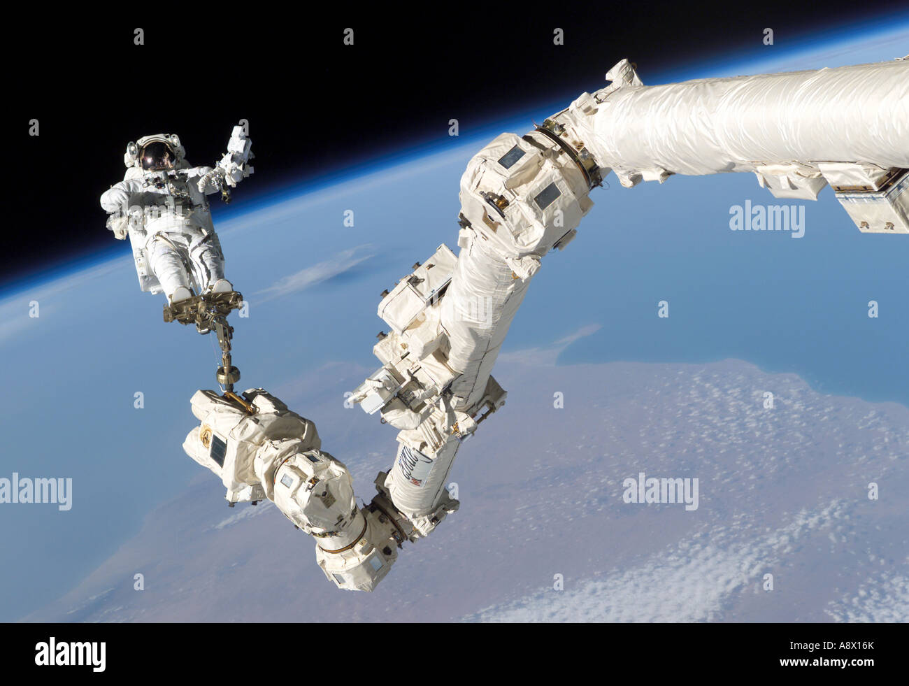 Astronaut Stephen K Robinson anchored to a foot restraint on the International Space Stations Canadarm2 Stock Photo