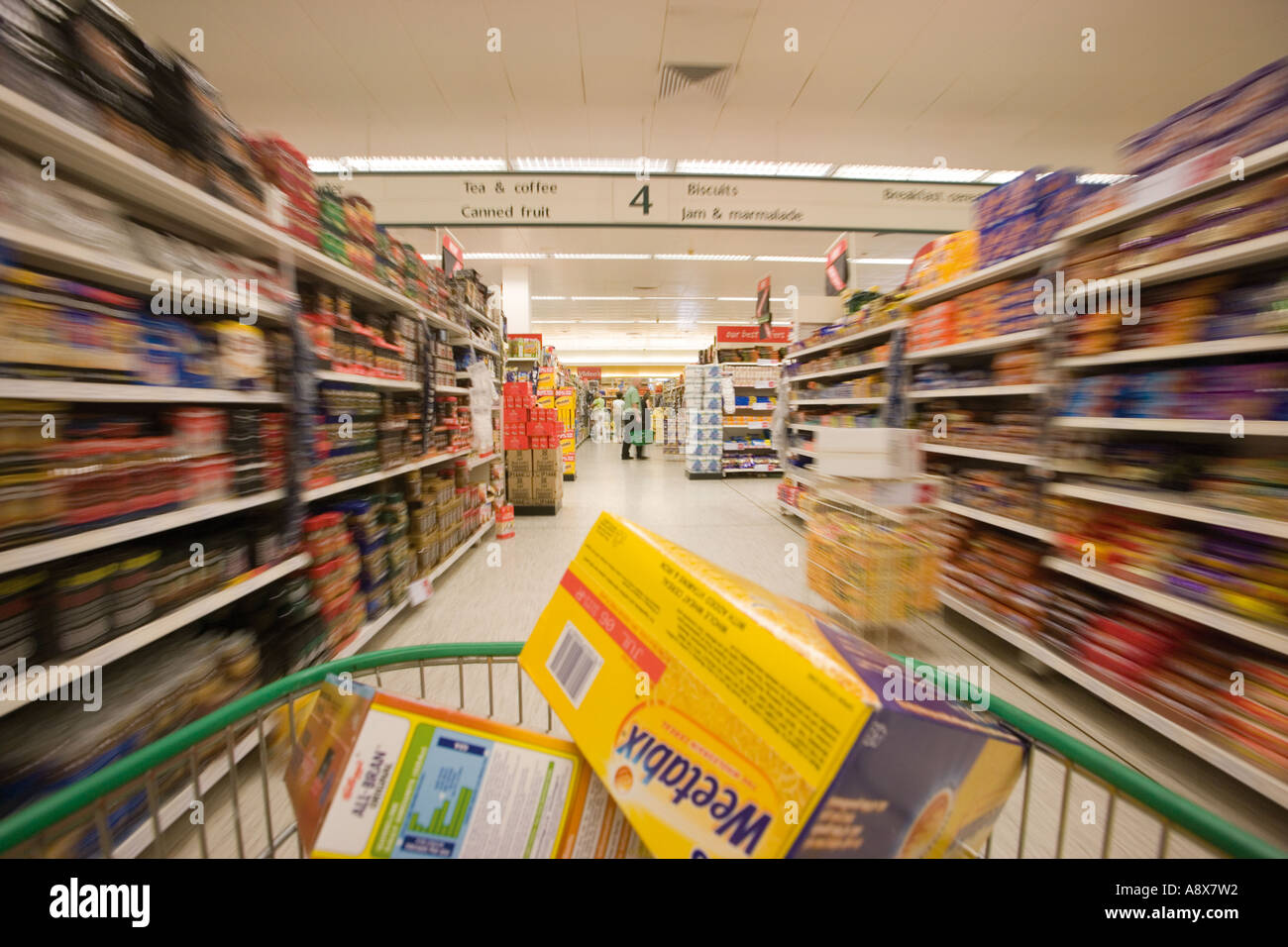 Supermarket trolley full of products in aisle.  Customer point of view. - Stock Image
