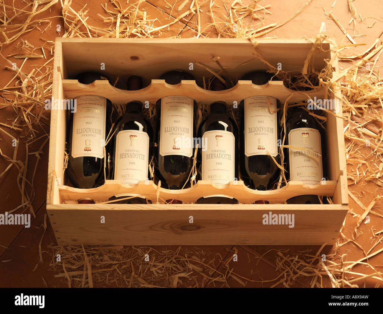 Bottles Of Red Bordeaux Wine In A Wooden Wine Box On A Bed