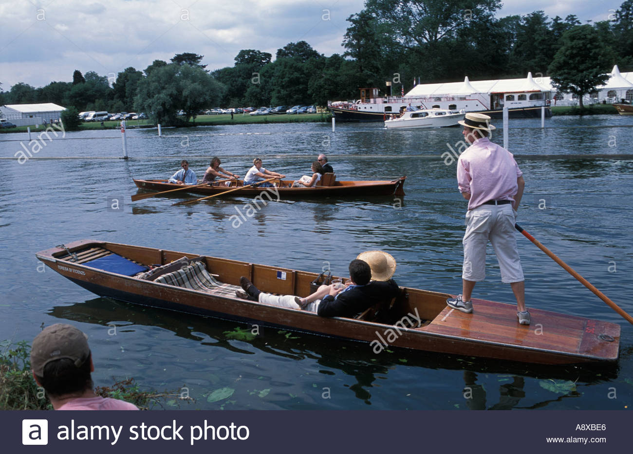 Visitors punting and rowing beside the Henley Regatta course, UK - Stock Image