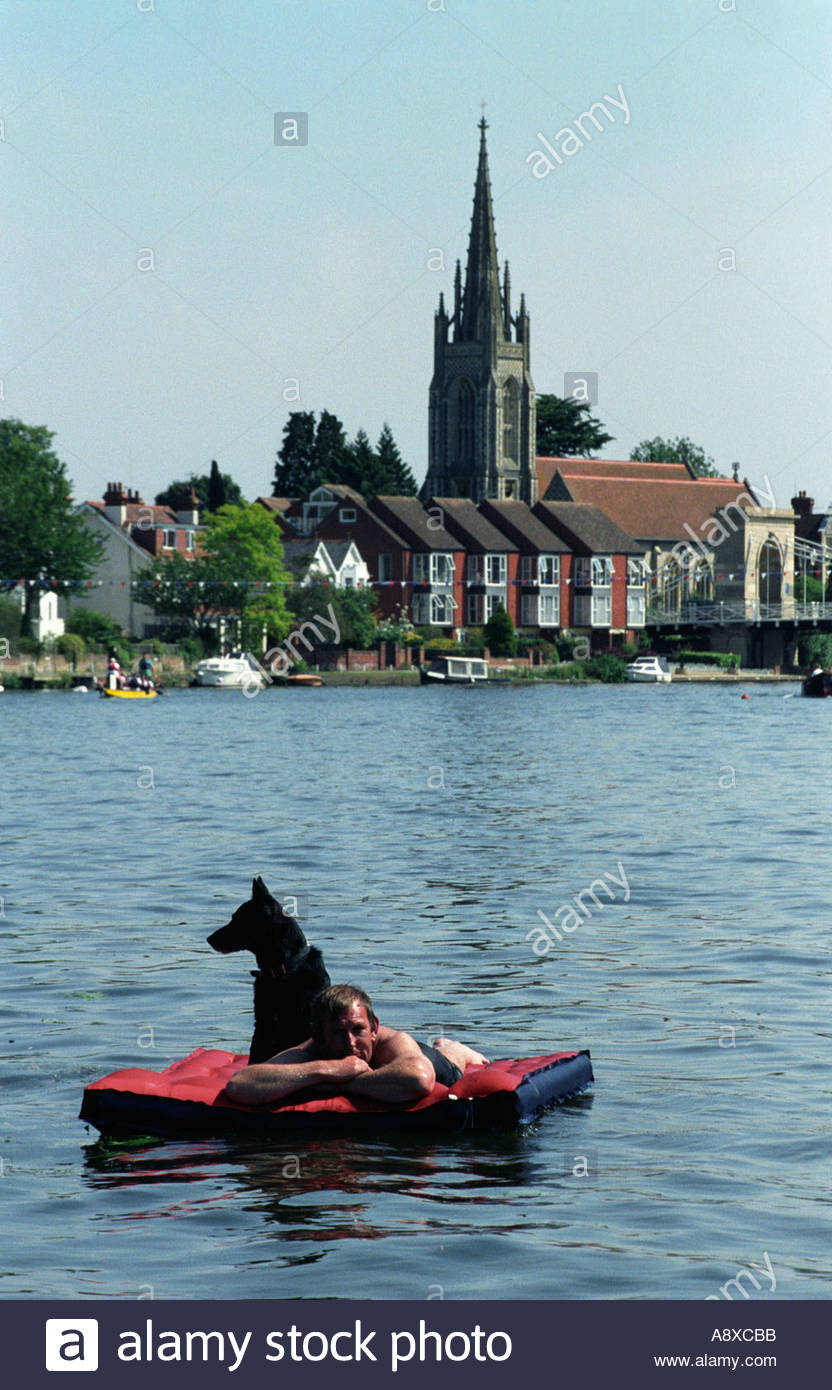 Sunbather and dog on inflatable raft at Marlow during the town's Regatta , UK - Stock Image