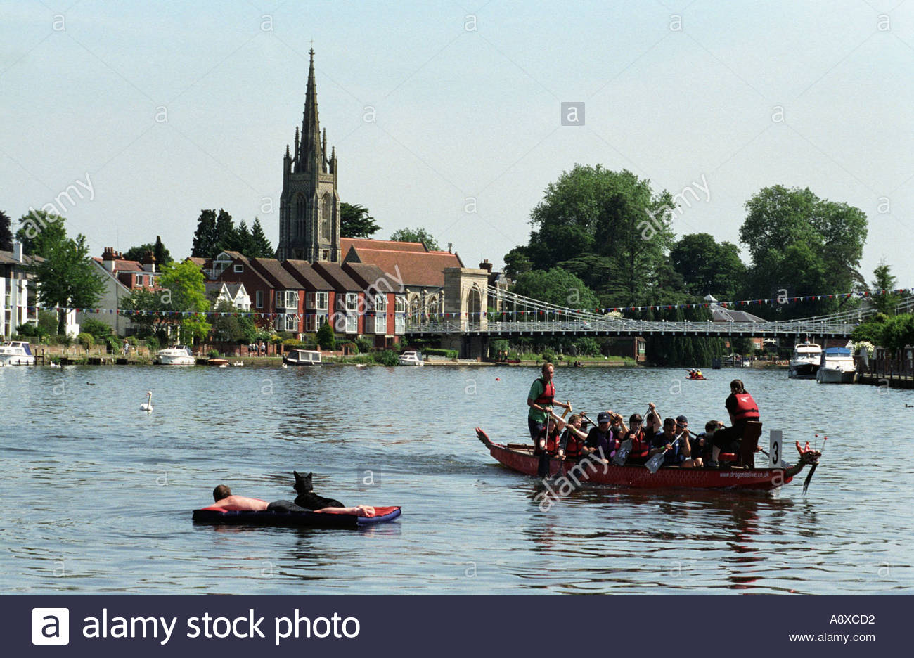 Dragon Boat racers and a lone floating sunbather at Marlow, on River Thames, UK - Stock Image