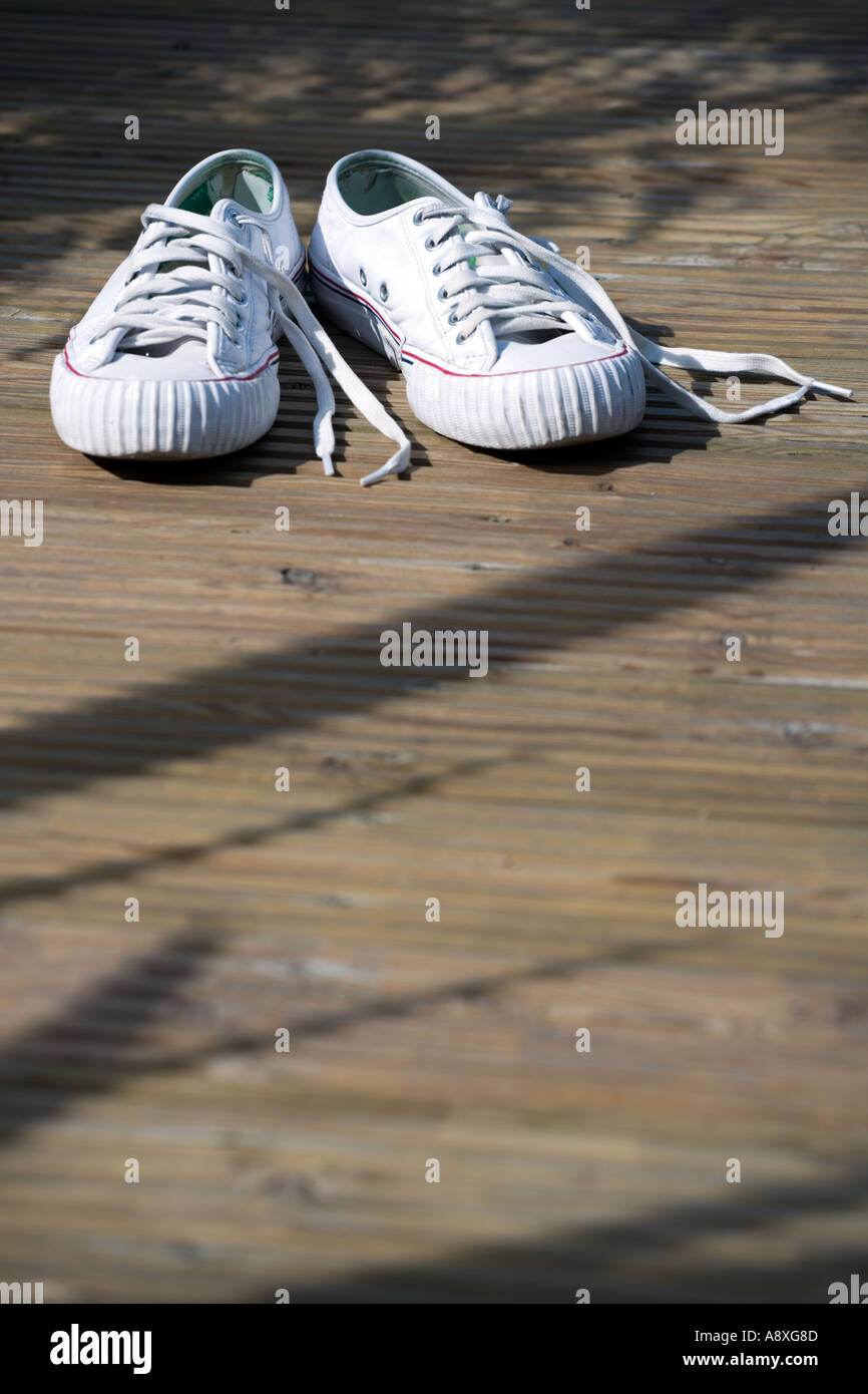 OLD SNEEKERS LYING ON GARDEN DECKING - Stock Image