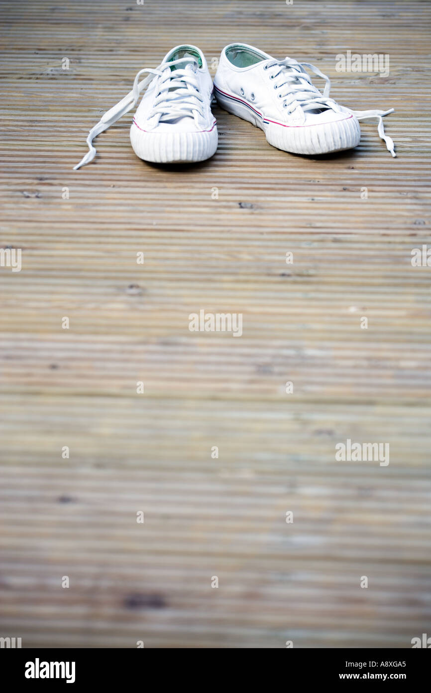 OLD SNEAKERS LYING ON GARDEN DECKING - Stock Image