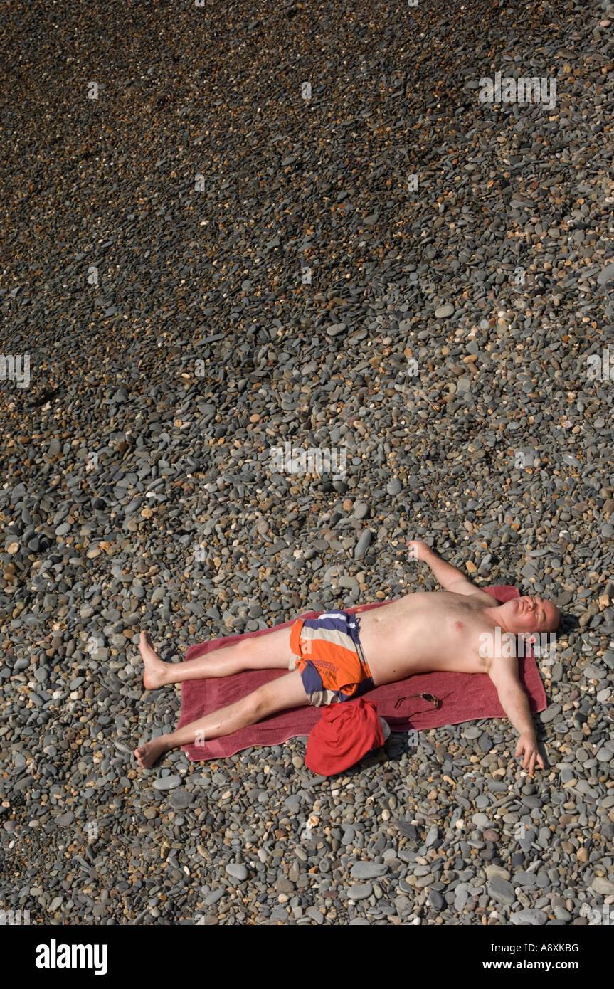 Man lying spread eagled on pebbles stony beach sunbathing Aberystwyth on a hot summer afternoon - Stock Image