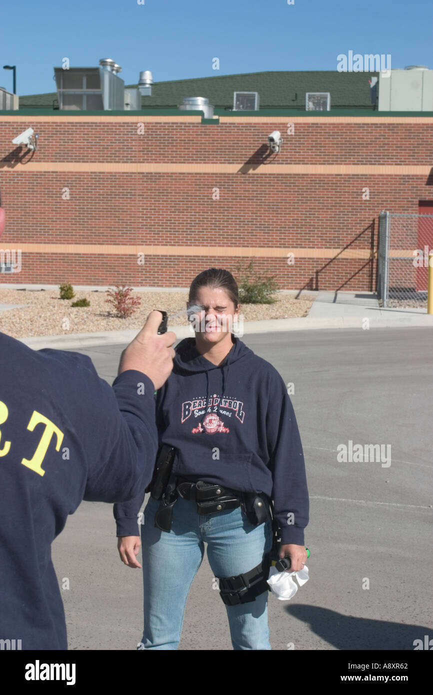 Female police officer getting sprayed with pepper spray training solution during training - Stock Image
