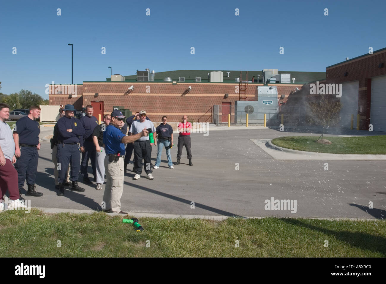 Instructor demonstrates pepper spray for a group of law enforcement and prison officers - Stock Image