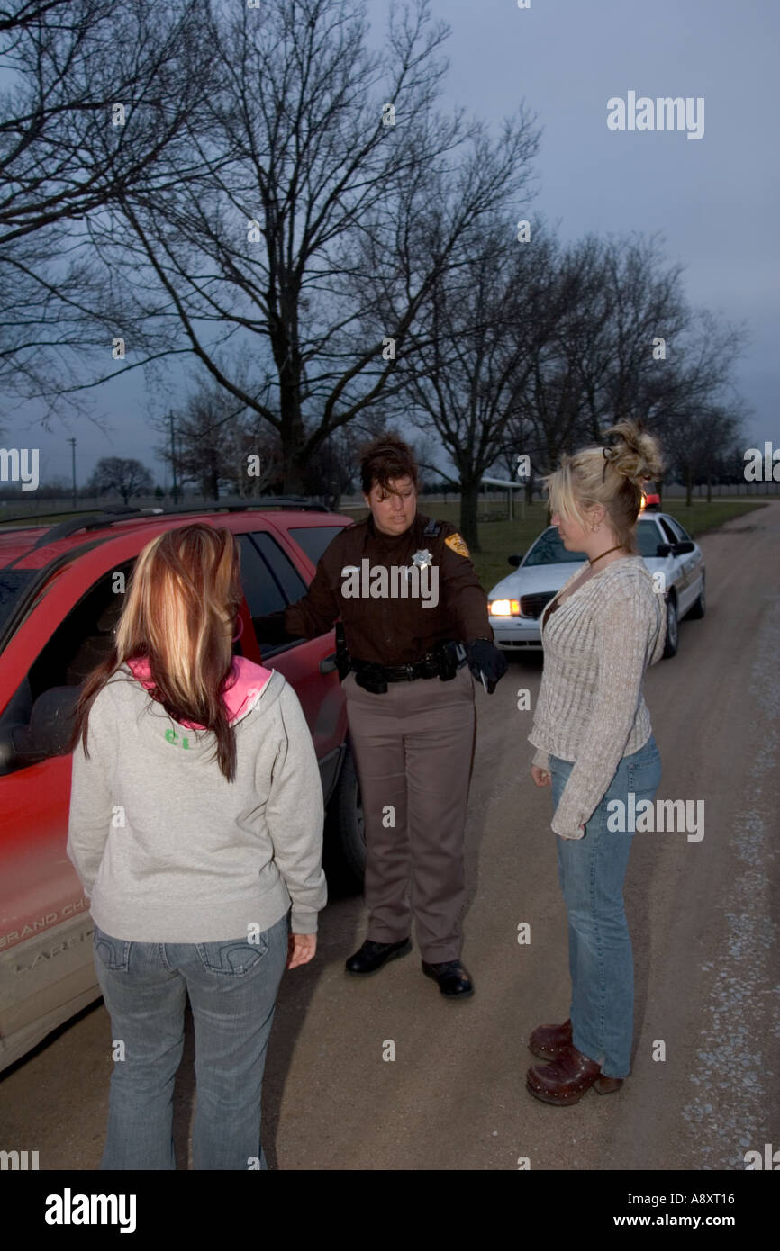 Female deputy talking to two minors that have been found in possession of beer - Stock Image