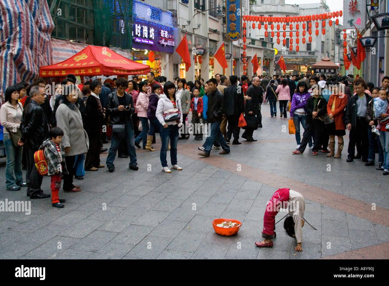 Chinese Girl Street Performer and Beggar Shang Xia Jiu Square a busy pedestrian shopping mall in Guangzhou China - Stock Image