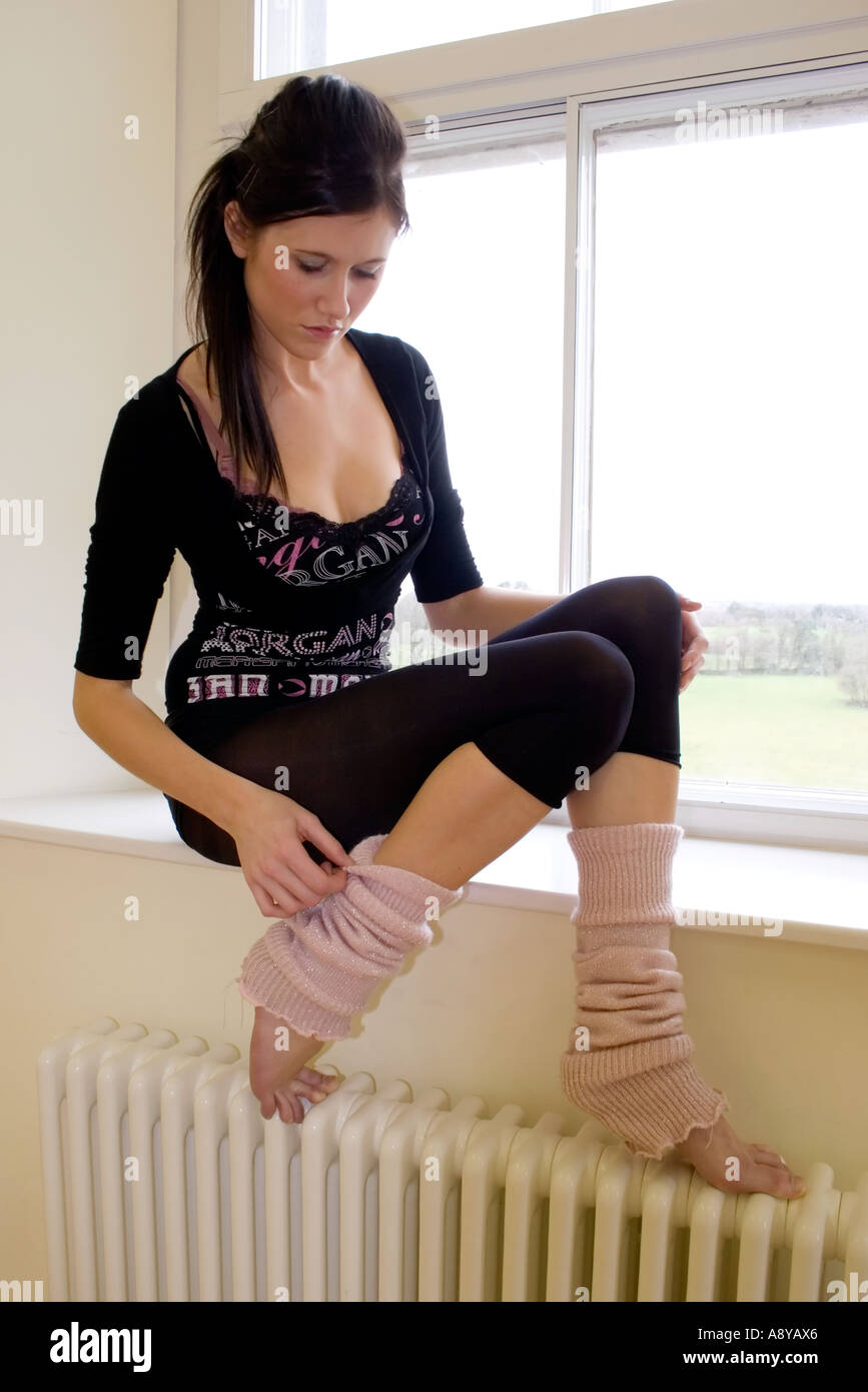 Dancer in leotard and leg warmers sitting in a window - Stock Image f00a2c38224