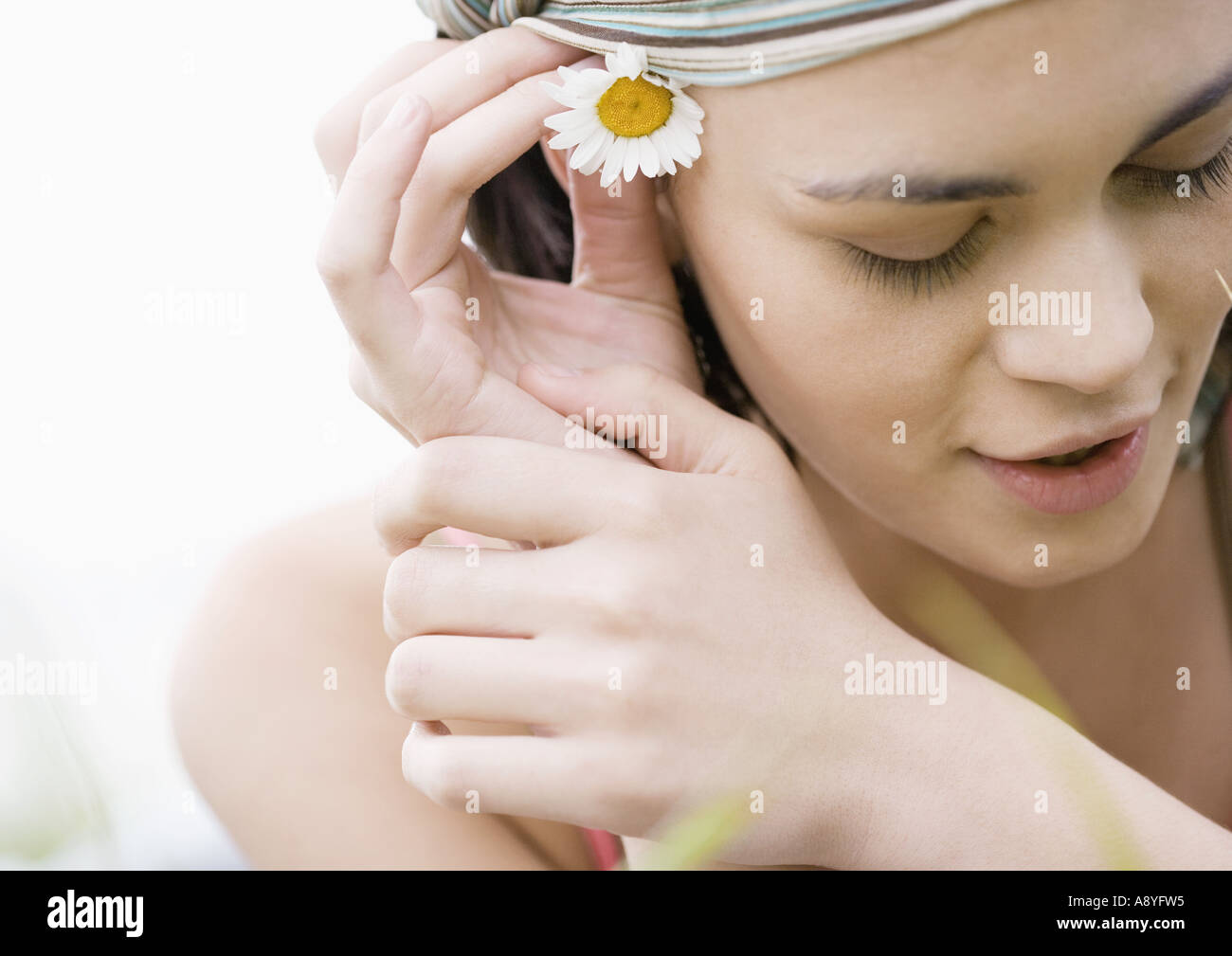 Flower behind ear stock photos flower behind ear stock images alamy young woman putting flower behind ear stock image izmirmasajfo