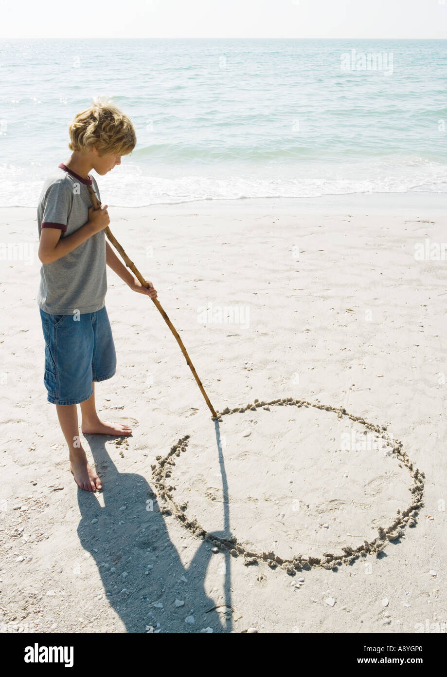 Boy drawing circle in sand - Stock Image