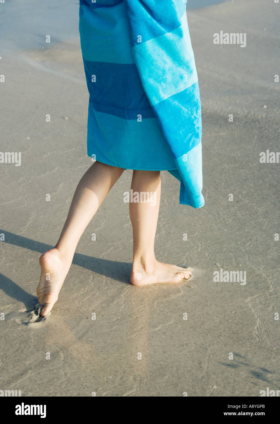Child wrapped in towel walking on wet sand - Stock Image