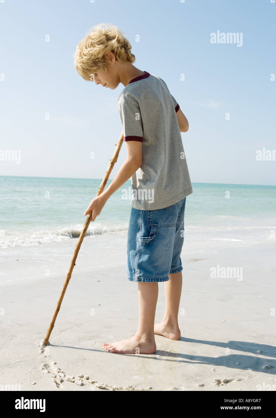 Boy drawing with stick on sand - Stock Image
