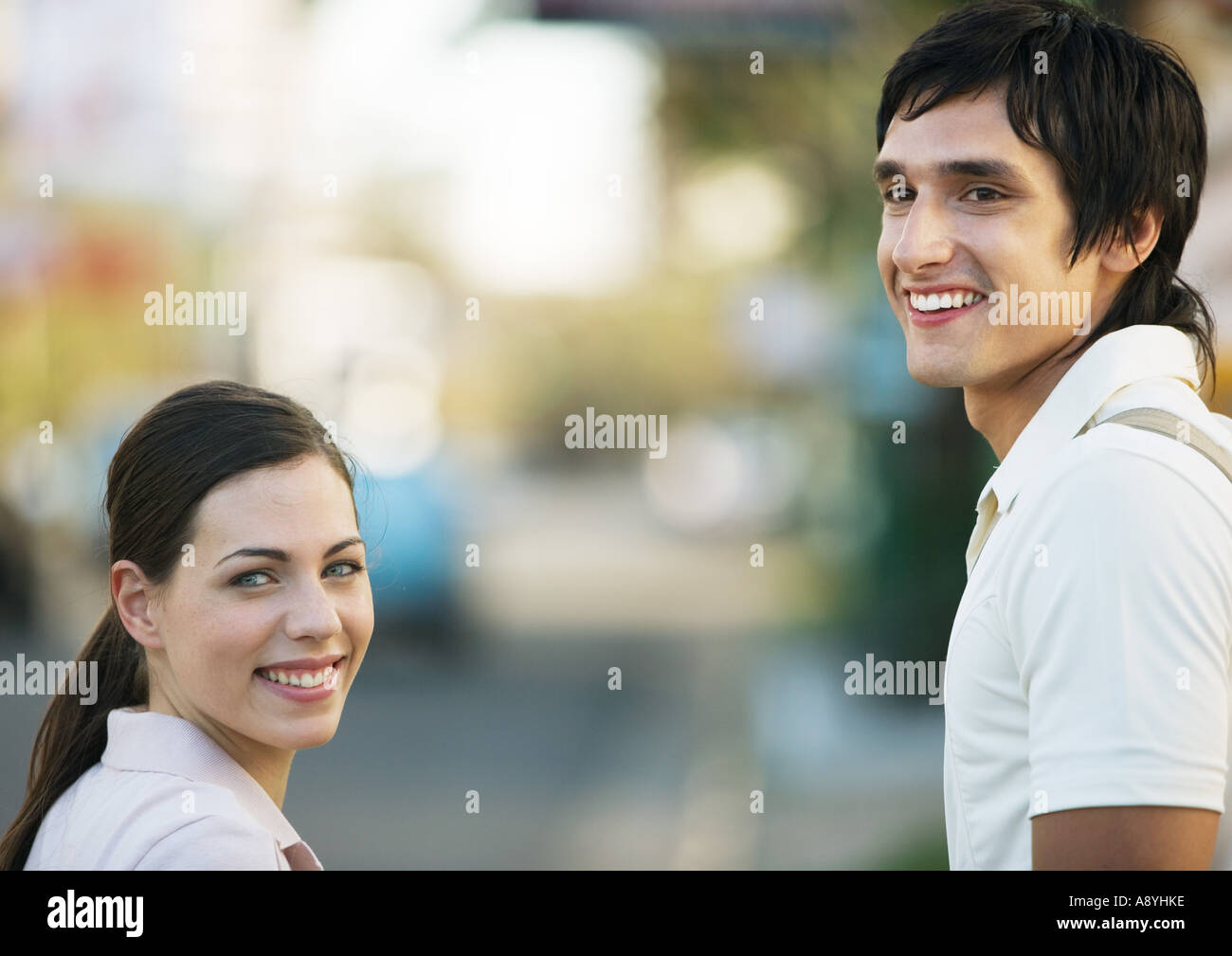 Young couple looking over shoulders, smiling - Stock Image