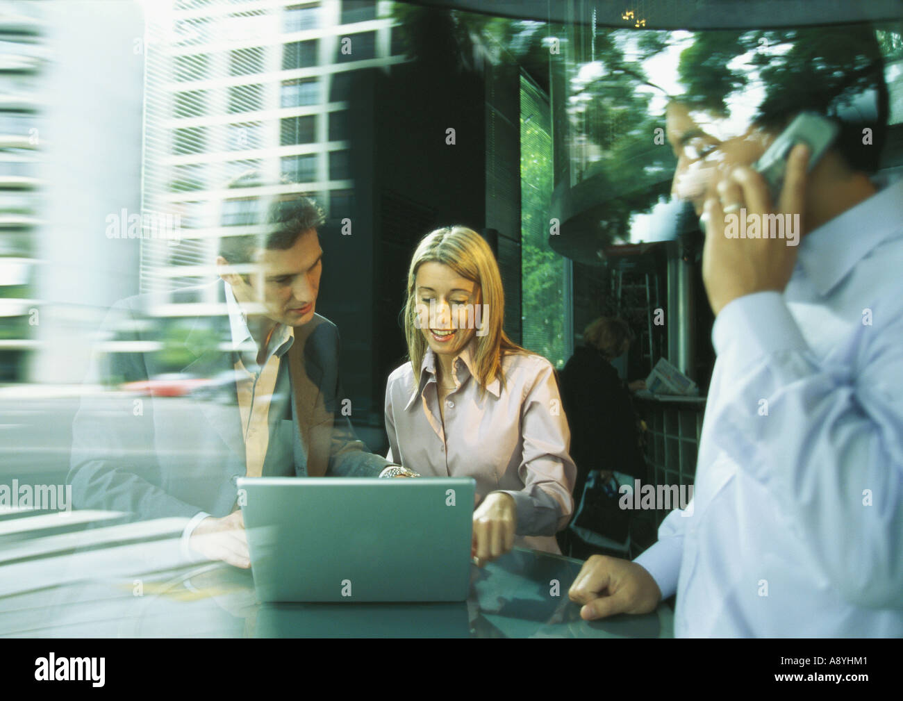 Businessman and businesswoman using laptop while second man uses cell phone - Stock Image
