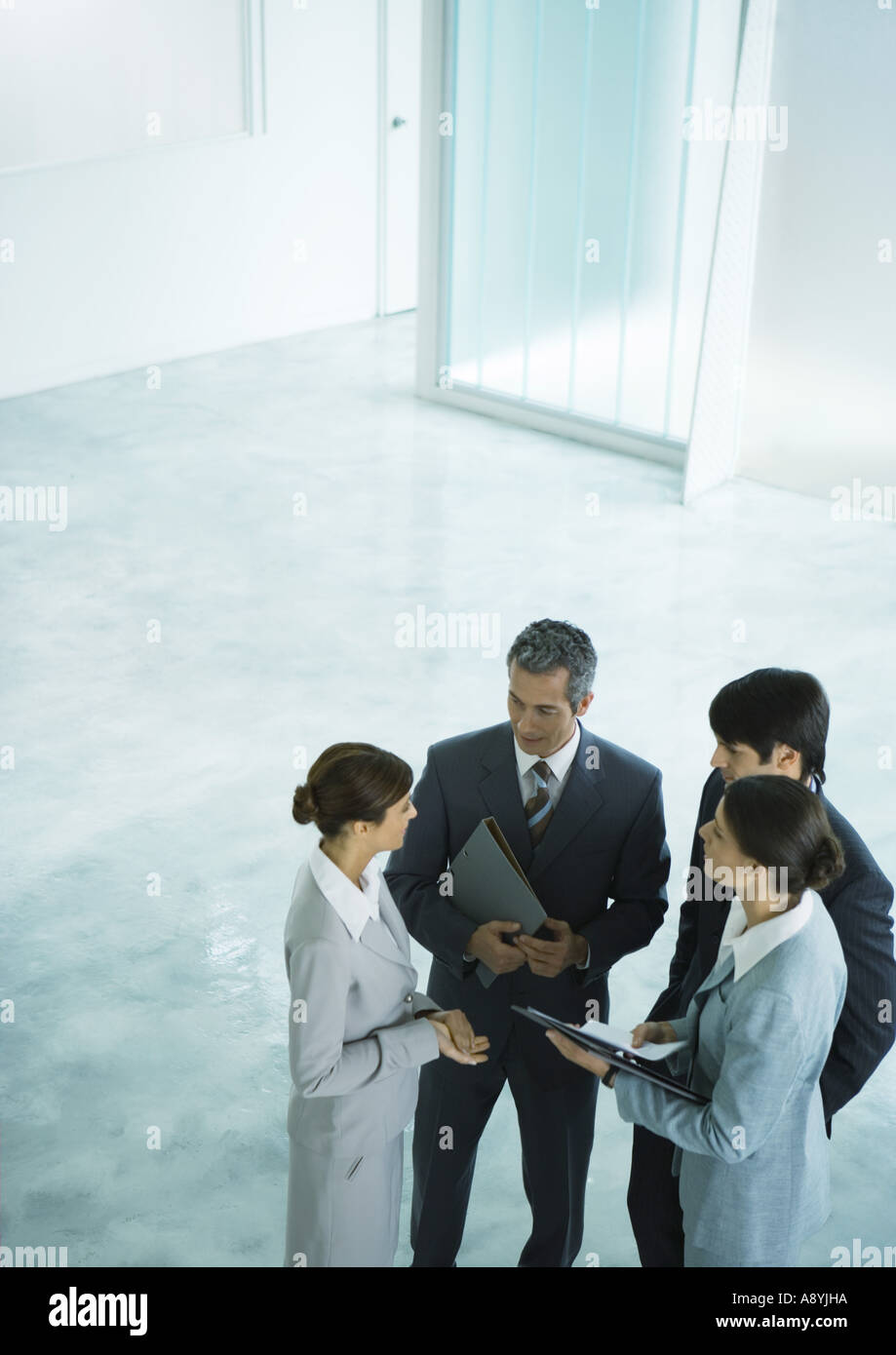 Four business associates talking together in lobby - Stock Image