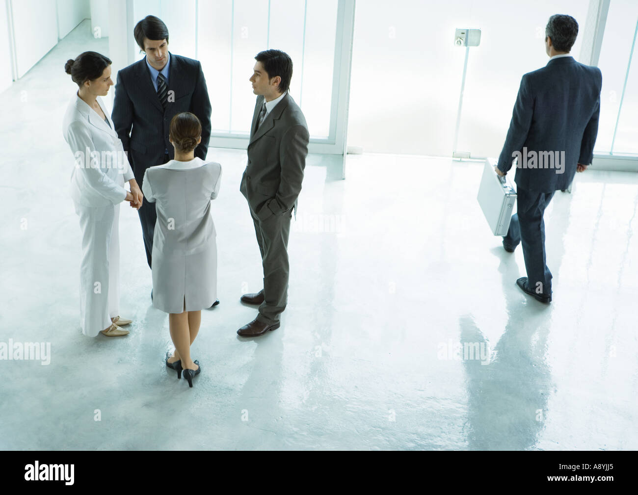Group of business people standing in lobby, talking - Stock Image
