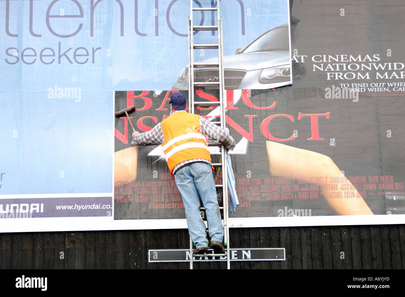a male worker pastes a new advertisment to a billboard stock photo