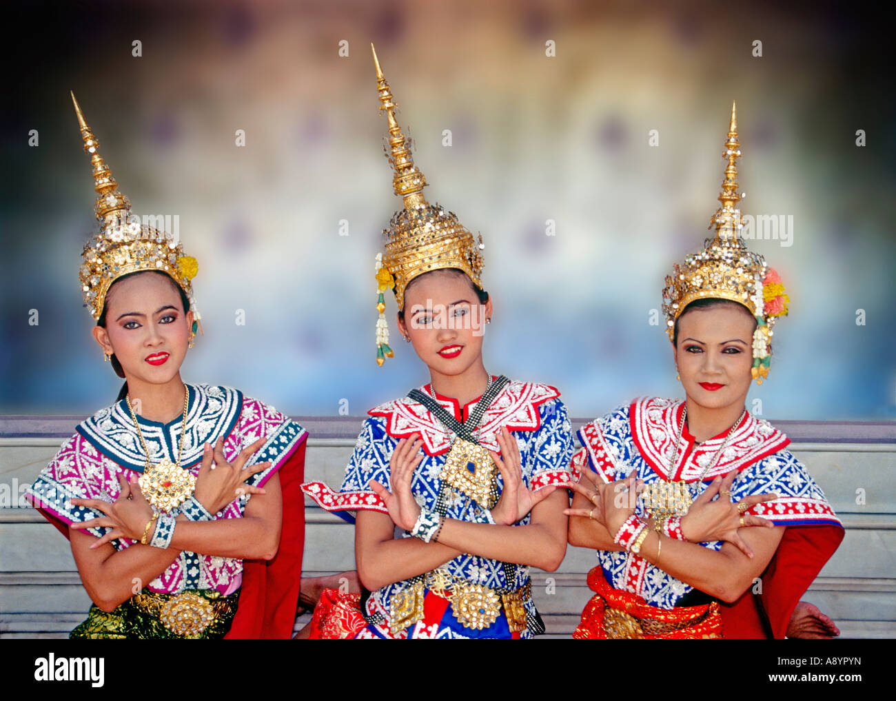 Three young female Thai traditional classical dancers demonstrating arm hand and finger movements in the temple - Stock Image