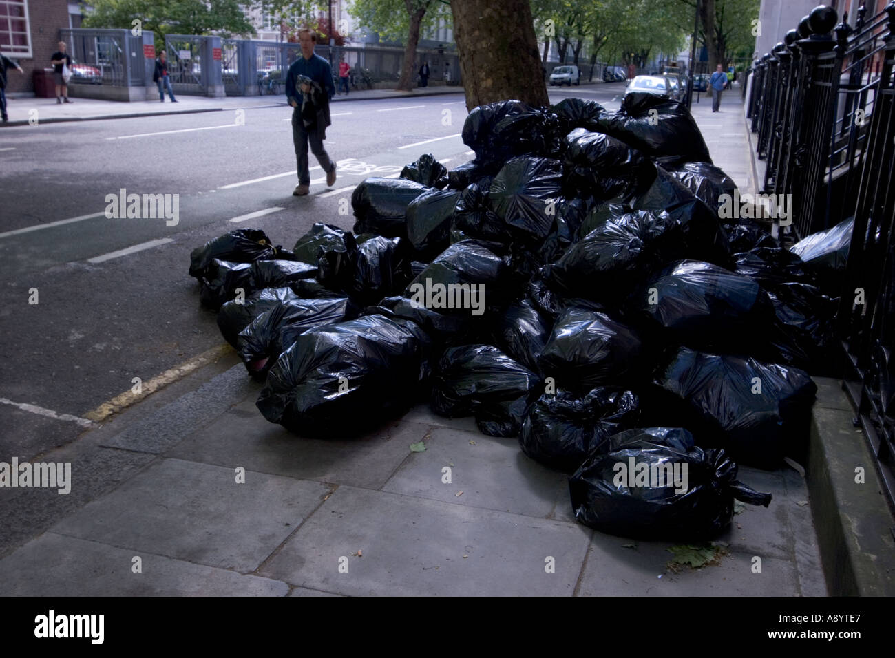 Rubbish bags full of household waste and litter blocking pavement in central London street - Stock Image