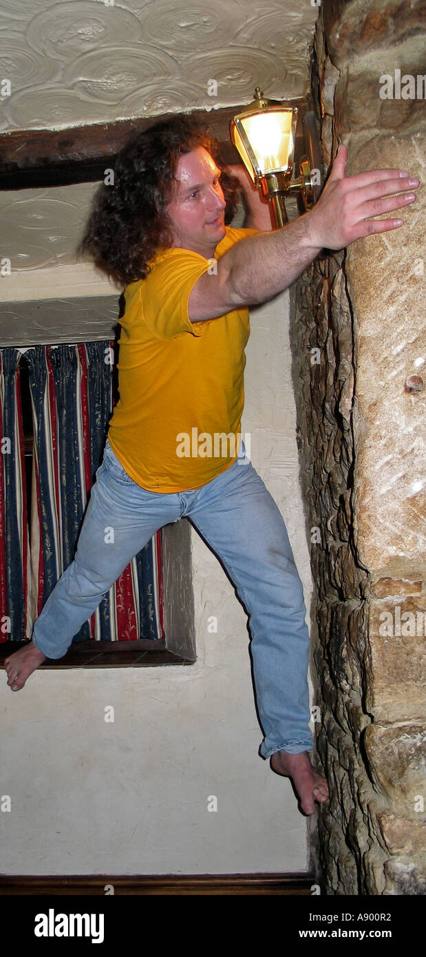 Young men indoor climbing the walls in an Inn after a few beers during a stag party weekend - Stock Image